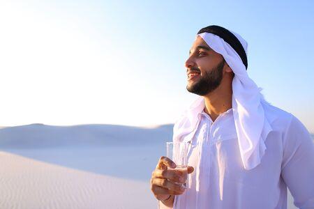 El joven árabe majestuoso sacia la sed con un vaso de agua fría y siente afluencia de fuerza y ??energía, sonríe y mira a un lado, de pie en medio de interminables desiertos arenosos con pura arena blanca al aire libre en la cálida mañana de verano. Musulmán moreno con oscuridad corta
