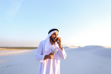 Arab young sheikh calls to friend or business partner and with smile on face and joy in eyes tells about winnings and amount of money in hands, rejoices and recounts bills standing in middle of bottomless desert with white sand on sunny summer day. Swarth Stock Photo