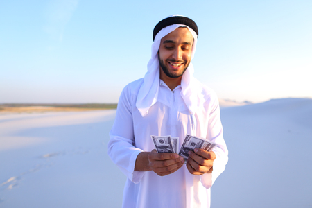 Handsome young Emirate in reckless mood recounts and examines banknotes, can not believe in own happiness or mirage, smiles and laughs throwing money down wind, standing in middle of bottomless desert with white sand on sunny summer day. Swarthy Muslim wi