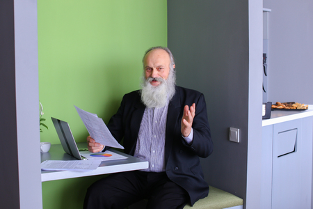 interbank: Senior citizen analyzes financial situation of company and conducts operations on interbank loans market using computer and negotiating headset while sitting in stylish office cafe on sunny day. Elderly man with long gray beard of European appearance dres