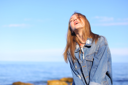 Beautiful young woman with small smile on lips looks at camera and smiles with broad smile, looks at camera and plays with eyes and eyes. young European-looking woman with blond mid-length hair dressed in blue denim jacket underneath which white sweater w Stock Photo