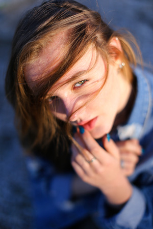 concep: Cute girl with serious facial expression posing on camera putting hair on face against blue sea and sky on warm clear day. Woman of European appearance with medium brown blond hair dressed in blue denim jacket and white jacket with bright pictures. Concep