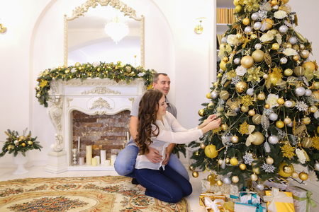 tenderly: Young love each other husband and wife together decorate Christmas tree and hang bright Christmas toy on branch. Young family on threshold of New Year holidays, and smiling tenderly embrace each other sitting on carpet near beautiful decorated Christmas t Stock Photo