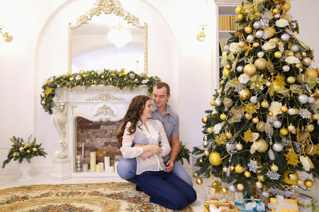 Lovers man and woman, young family tenderly embrace each other and kiss, pose for photograph sitting on carpet near beautiful decorated Christmas tree and fireplace with candles in bright and comfortable room. Cute female with long dark wavy hair dressed  Stock Photo