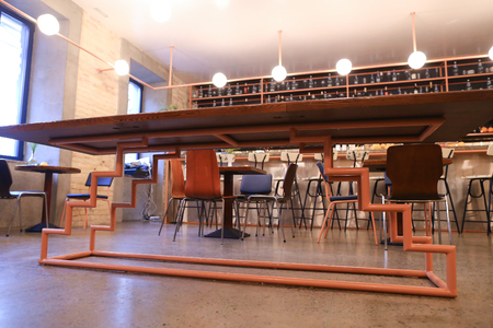 In middle of establishment, cafe or restaurant table with wooden lacquered top on unusual metal stand of orange on background of high bar with stones and lots of drinks and lots of glasses, bar in stone with high chairs in marble. Cozy quiet setting illum Editorial
