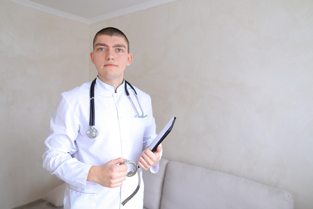 Handsome male specialized doctor poses on camera in good mood and smiles, loves work and gives advice with folder and centimeter tape in hands, and stethoscope on neck and  standing in bright medical cabinet. Guy physician  European-looking with short hai