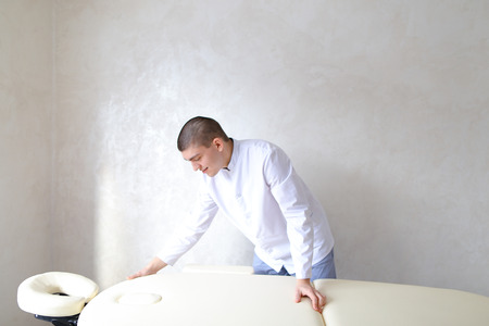 Cute guy therapist and masseur puts out beige couch and waits for clients or advertises services of salon, standing near couch in middle of room during day. Man physician European-looking with short haircut dressed in white medical uniform. Concept of peo