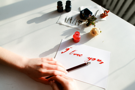 Female master of calligraphy and lettering creates red ink and pen fountain with wonderful love valentines with text I love you on day of all lovers on light table with accessories for lettering, small jars with colorful mascara and decorations in art stu