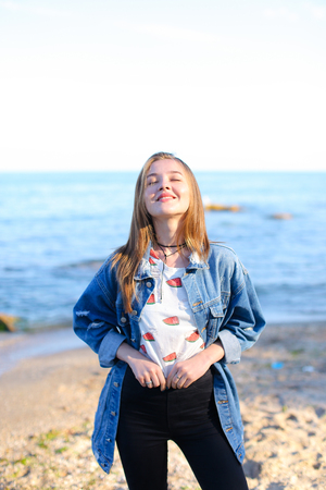 Lovely girl poses positively on camera in perfect mood, smiles and laughs sweetly, slowly approaches very shore of water, squints from sun and admires incredible scenery around, standing on beach of sandy beach on warm summer evening at sunset. woman of E