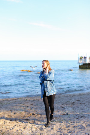 Pretty young woman turns face to camera and looks into camera lens with gentle look and smile, straightens hair with hand and enjoys sea view, standing on shore of blue bottomless sea on clear evening. woman of European appearance with medium brown blond