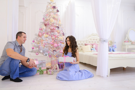 Young parents happy husband and wife take out from under Christmas tree with gift boxes and give each other from heart. Family on threshold of New Year holidays smile and kiss each other. Cute female with long dark wavy hair dressed in long blue dress, ha Stock Photo