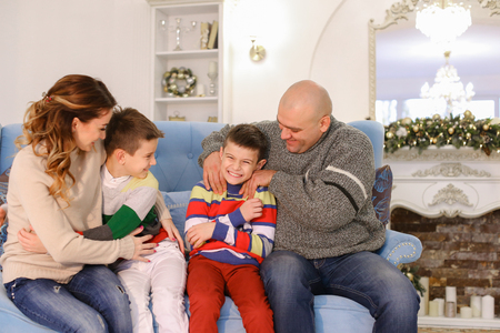 family tickle: Large and friendly family laughs and rejoices at New Years holidays, loving parents affectionately tickle and family-like hugs boys of children, twin brothers, sitting on blue sofa with beautiful pillows christmas decorated with tall Christmas tree and fi