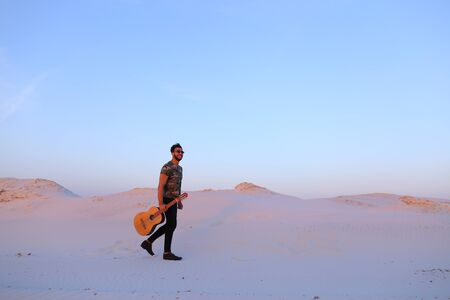 Happy and successful Arab male musician chooses beautiful place to play guitar and walks around desert sand with musical instrument in hands of warm summer evening at sunset. Swarthy man with dark hair and short haircut in sunglasses dressed in camouflage Stock Photo