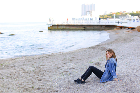 Relaxed and charming woman looks away with beautiful and easy smile, turns head to water and enjoys quiet evening, hypnotized by incredible sea view, reclining on sandy beach and looking toward endless blue sea on pleasant evening.Young European-looking w Stock Photo