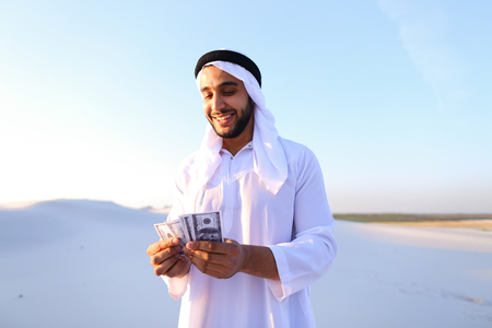 Handsome young Emirate in reckless mood recounts and examines banknotes. Stock Photo