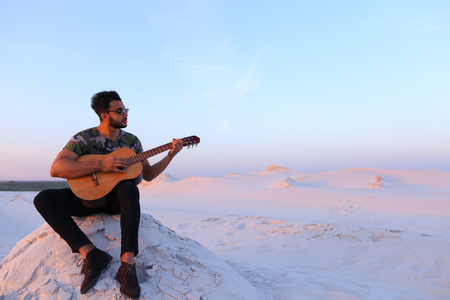 Bearded Muslim young man enthusiastically plays guitar and learns to take new chords or increases level of playing skills on musical instrument, sitting on hill in middle of wide sandy desert on warm summer evening at sunset. Swarthy man with dark hair an