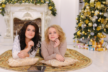 Cheerful young women friends look at camera lens and smile, laugh and rejoice at upcoming holidays. Women hold credit card and tablet in their hands, show thumbs up, lying on floor on carpet in spacious living room with fireplace and tall New Year tree on Stock Photo