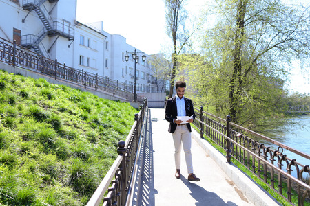 Attractive person talks by phone and walking on bridge. Man joyfully puts hands up with papers. Guy has short dark hair, beard, sunglasses on pocket and dressed in black jacked, white jeans. Concept of modern technologies fast work of Internet free calls  Stock Photo