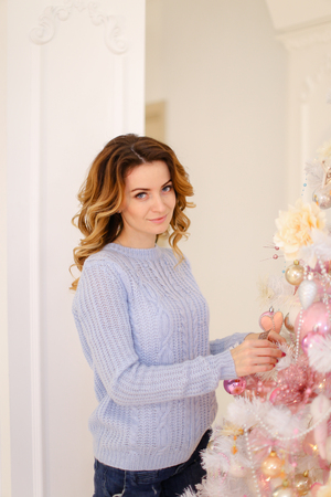 Pretty woman decorates Christmas tree and hangs bright toys and balls, prepares for arrival of guests for new years meeting and stands on background of white wall in bright bedroom. European-looking girl with long curly hair dressed in blue sweater and bl Stock Photo