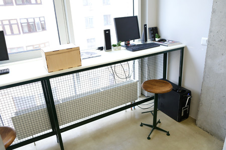 Minimalist interior in work area. Simple and long table with white table top and black supports with grid on which computers with columns and keyboards are standing, next to table chair with wooden seat and metal black base on wheels. Room or office with