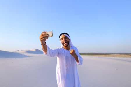 Happy, handsome guy, emirate and tourist, conducts dialogue through Internet with help of device, waves hand and smiles at camera of smartphone, shows beautiful views and sights of large sandy desert outdoors on summer day. Swarthy Muslim with short dark hair dressed in kandura, long, spacious dress made of white unpainted cotton with knitted lace cap of hafia, on top of which headscarf and dark brown shoes are tied. Concept of Arab and Muslim men, modern technology and gadgets, united Arab emirates and beautiful landscapes, sheikh in desert and seclusion with nature, national clothes and traditions. Stock Photo