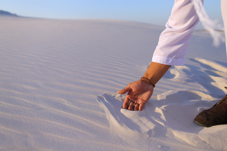 Close-up of face and hands of young Muslim man who takes sand into hand and blows small white grains of sand through fingers, guy smiles and looks out into distance of bottomless desert on hot summer day. Swarthy, handsome Muslim with short dark hair dressed in kandura, long, spacious dress made of white unpainted cotton with knitted lace cap of hafia, on top of which tied goutrail and dark brown shoes. Concept of Arab and Muslim men, united Arab emirates and beautiful landscapes, peace and tranquility, national clothing of emirates.