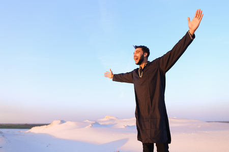 Shooting of attractive Muslim guy who smiles with broad smile and looks around. Young sheikh guy spreads hands to sides and shows gesture of successful man, standing among bottomless desert with hills of white sand on clear evening. Beautiful Emirate with short dark hair dressed in black kandura, long spacious dress made of dark cotton and dark brown shoes. Concept of Arab and Muslim men, united Arab emirates and beautiful landscapes, sheikh in desert and seclusion from nature, Emiratis national clothes, good mood and enjoyment of life.
