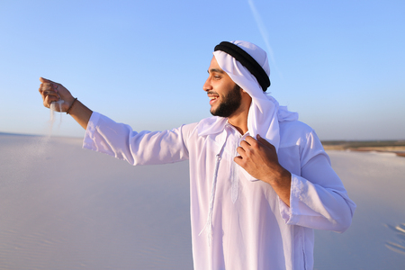 Young Arab guy who takes sand in hand and lifts it to smiling face and blows through fingers fine white grains of sand in bottomless desert on hot summer day. Swarthy, handsome Muslim with short dark hair dressed in kandura, long, spacious dress made of white unpainted cotton with knitted lace cap of hafia, on top of which tied goutrail and dark brown shoes. Concept of Arab and Muslim men, united Arab emirates and beautiful landscapes, peace and tranquility, national clothing of emirates.