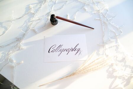 Inscription Calligraphy made in italic fine print on rectangular white sheet of paper, next to table small jar with black ink and fountain pen on light table with flickering garland. Concept of fine art and liquid paints or mascara, beautiful writing, calligraphy and lettering, materials and tools, craftsmanship and hobbies.