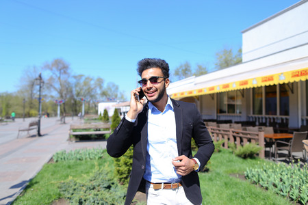 Italian man talking by phone and laugh in a crowed place. Attractive guy has short dark hair, beard and dimples on cheeks. Person dressed in black jacked. Concept of new technologies free calls, always in touch good relationship apps for talking.