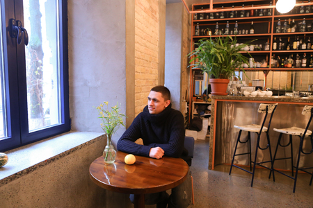 Attractive guy sits at cafe or restaurant table, laughs and poses, looks at photographer in background, tall bar with mirrors and lot of drinks and lot of glasses, bar in stone with high marble chairs. Cozy quiet establishment illuminated by warm light of Editorial