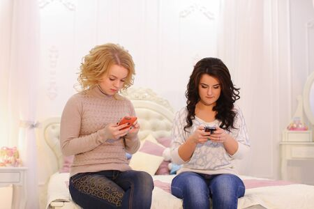 Attractive women look at screens and drive their fingers through gadget sensor and correspond with friends in social networks or read news, laugh and smile at each other. 版權商用圖片