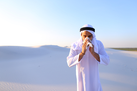 Sad handsome young man, sheikh ill with cold and feels unwell, eases breathing with handkerchief and looks to side, standing in middle of bottomless desert with snow-white sand on sunny summer day.