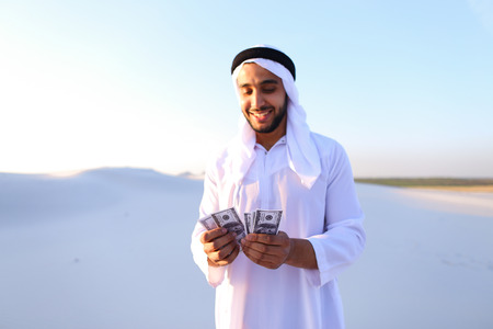 Handsome young Emirate in reckless mood recounts and examines banknotes, can not believe in own happiness or mirage.