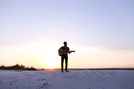 Handsome Arab young guy learns to play rock music on musical string instrument, sings and drives guitar strings, standing on sandy hill desert on warm summer evening at sunset. Stock Photo