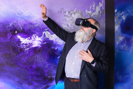 Elderly man in VR glasses outside imagination felt virtual reality and enjoys seen and new technologies. Old man with long gray beard of European appearance dressed in black classic suit and white shirt in blue stripes and stands on background of bright colored wall in blue and purple tones in premises of modern cafe. Concept of advanced elderly person, sense of virtual world, modern gadgets and technology, innovation and virtual games.