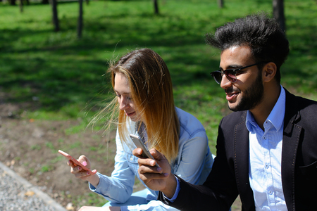 Two people show furniture on phones and laugh. Handsome boy has dimples, full lips and dark hair. Woman has long fair hair and dressed in denim shirt and white T-shirt. Concept of modern technologies online stores apps for shopping wifi and free Internet. Stock Photo