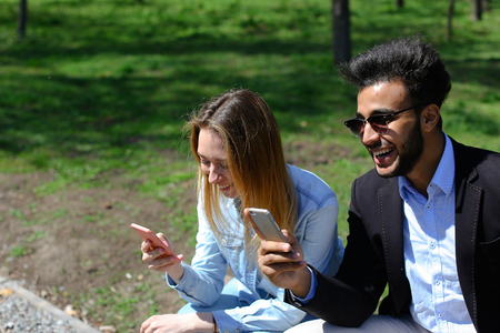 Siblings looking at phone s screen, man leaf photos. Lady has beautiful long hair and dressed in denim shirt, white T-shirt. Good looking man has beard, short hair and dimples on cheeks. Concept of traveling good camera modern technology