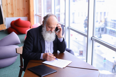 Retired old man give call to business partner with smart phone using new technology todeal with financial matters in summer in office. Handsome stately grey head man withlong beard in business suit sitting at table in studio in modern workspace. Concept ofsuccessful business in old age pension, old Boss Head continues to deal on pensions,old professors teach at university education, transfer of experience from old generation.
