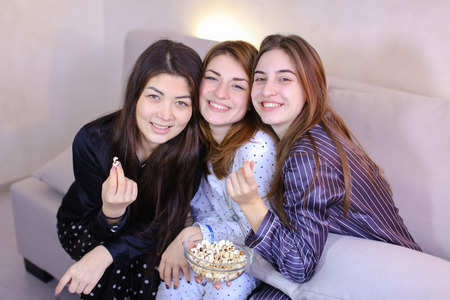 Three wonderful women have fun, laugh and talk on girlish themes, pose in camera with smile on their face and eat popcorn, sitting on gray soft sofa in bright bedroom at night. European-looking girl with medium-length fair-haired hair dressed in light pajamas in polka dots, second girl with fair-haired hair dressed in purple pajamas in white vertical stripe, European-looking woman with black long hair dressed in black pajamas. Concept of beautiful and happy women friends, pleasant pastime for watching movies, hen party and cheerful mood, modern technology and gadgets, pajamas party and female friendship, advertising womens magazine, cheerful mood.