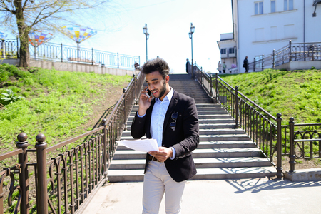 Young worker talks with boss by phone, holds work papers in hands. Secretary has short dark hair, beard and dressed in black jacked, white jeans. Concept of modern technologies part-full job always in touch
