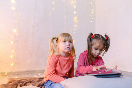 Cute little girls play in computer games on device or watch cartoons, press something on touch screen of tablet, smile and communicate with each other, sitting on rug in bright room with flickering New Years garland in evening. Blond girl of European appearance with tails on sides dressed in orange sweatshirt with long sleeves and blue jeans, small female brunette with two tails on each side dressed in raspberry sweater and blue jeans. Concept of happy and carefree childhood, modern technologies and gadgets, bright and unforgettable New Years childrens emotions, Christmas gifts and Santa Claus, childrens entertainment and fun games, decor and bright festive interior. Stock Photo