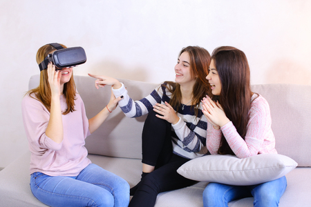 Attractive girls hold modern devices, VR glasses and inspect, study possibilities of gadget and communicate with each other. One of female friends put on VR glasses on head and plunged into parallel world, sitting on gray sofa in room during day. European-looking girl with medium-length blond hair dressed in pink blouse and jeans, second girl with fair-haired hair dressed in striped long-sleeved shirt and black pants, European-looking woman with black long hair dressed in pink sweatshirt with long sleeves and blue jeans. Concept of beautiful and happy female friends, modern technology and gadgets, hen party or pajama party, new interesting opportunities with VR. Stock Photo