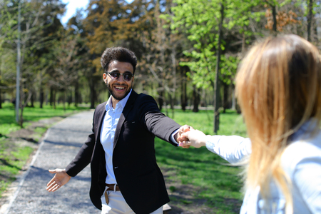 Woman following husband holds hand. Man has short dark hair, beard, dimples on cheeks and dressed in black jacket, blue shirt and white jeans. Concept of good conditions for young couples places for rest and clean parks.