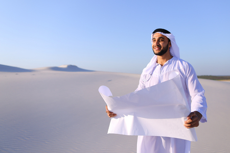 Beautiful Emirate Sheikh businessman studying project of future construction of complex, standing in middle of bottomless desert with white clean sand