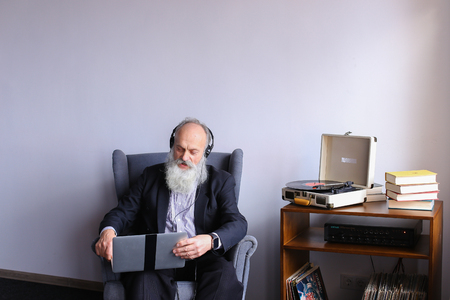 Modern oldster man delighted with sound of his favorite rock hits in headphones and enjoys listening to songs and searching for familiar tracks on Internet using laptop