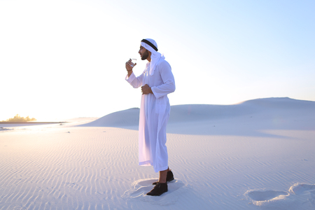 Stately Arab young man quenches thirst with glass of cool water and feels influx of strength and energy, smiles and looks to side