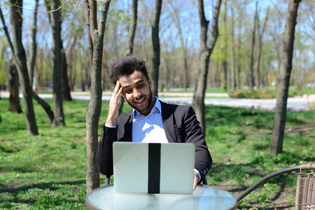 Unemployed sits by table and look at laptop s screen. Man has beard, short hair and dimples on cheeks, sunglasses in pocket. Concept of work in Internet wifi app for unemployed people. Stock Photo