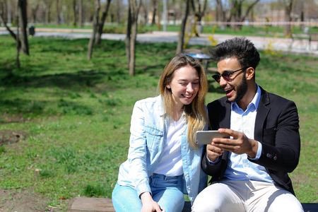 Young couple doing selfie on phone, smiling a lot, doing duck faces and showing peace finger sign. Wife has beautiful long hair and dressed in jeans and white T-shirt. Husband has beard, short hair and dimples. Concept of fast delivery of orders shopping in Internet and good camera