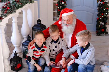 Gladden kids  receiving modern gadget from Santa Claus. Happy children satisfying with winter holidays. Concept of gifting devices for good boys by Father Christmas. Stock Photo